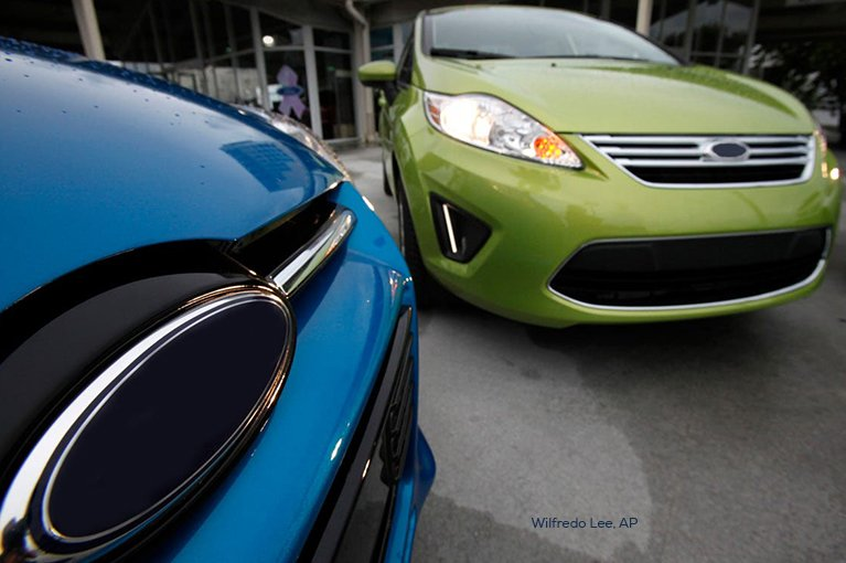 One green car is parked beside one blue car.
