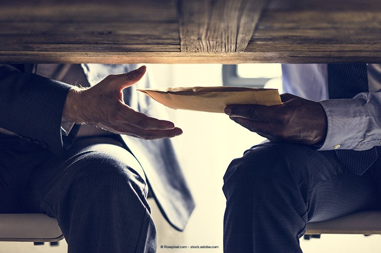 A man hands a manila envelope to another man under the table
