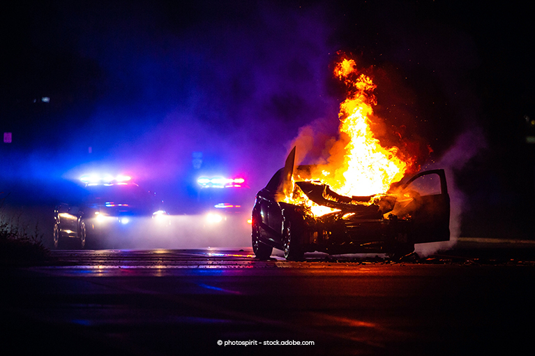 A fire bursts out of the engine of the car