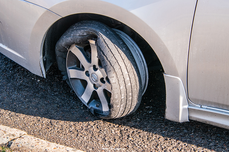 The wheel of a tire has not only gone flat, but also sustained further damage.