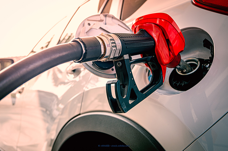 Alt text: A gas pump is putting gas into a vehicle's tank