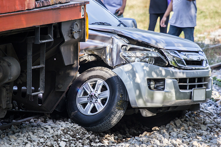 Alt text: A car is stopped on train tracks, crushed by an oncoming train.