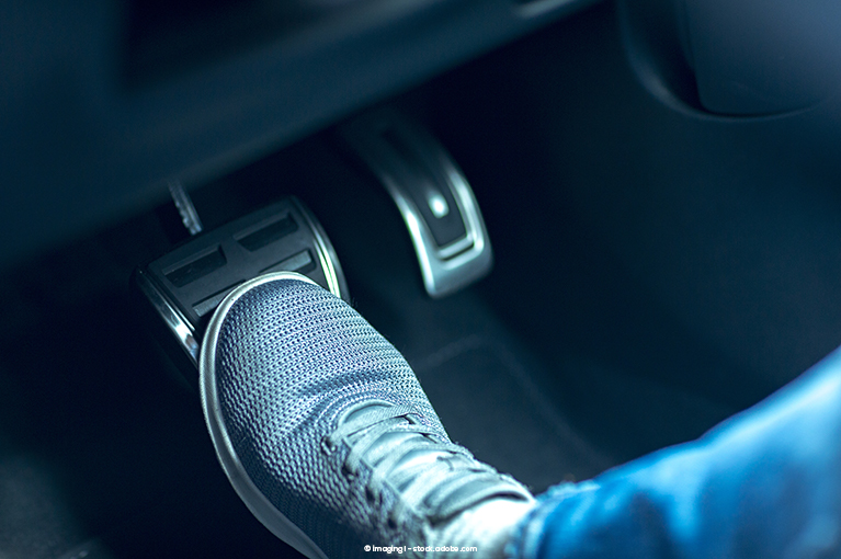 Alt text: A foot presses on the brake.