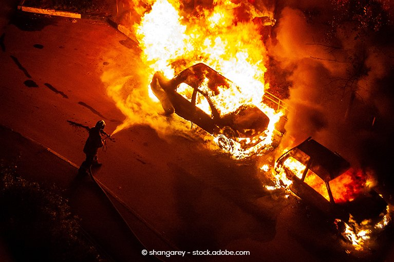 Photo description: Someone attempts to put out a car fire using a spray hose.