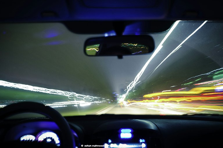 Photo description: From the perspective of a vehicle occupant, a vehicle speeds down a road and appears to shake while doing so.