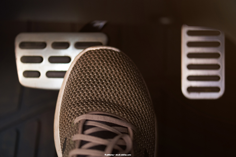 Photo description: A driver's foot hovers over the brake pedal.