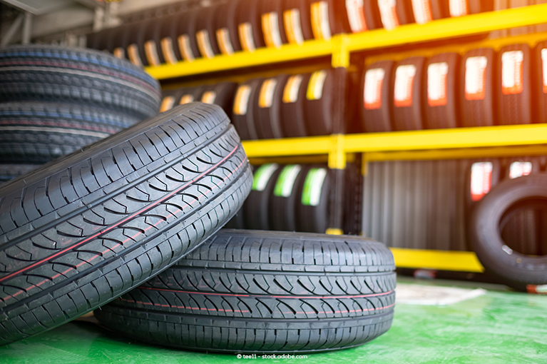 Photo description: Tires are stacked atop each other in the foreground, and rows of tires sit on shelves in the background.