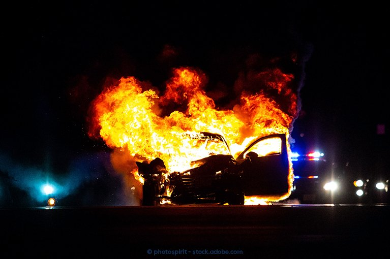 Photo description: A vehicle is consumed by flames.