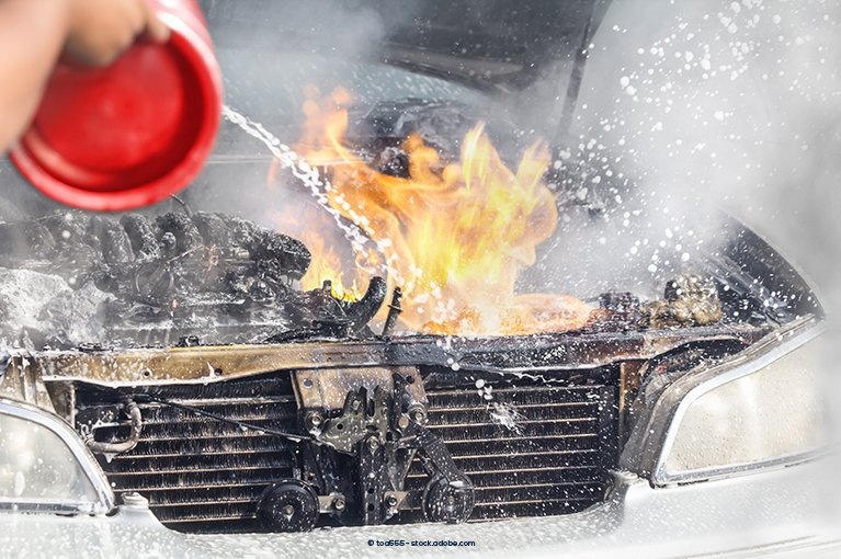 Someone pours water on a fire under a car hood.