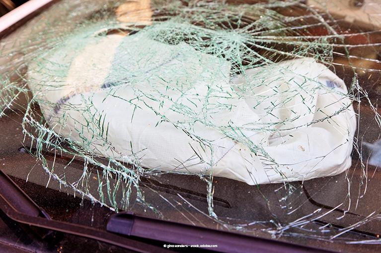 Photo description: A deflated airbag sits underneath a shattered windshield.