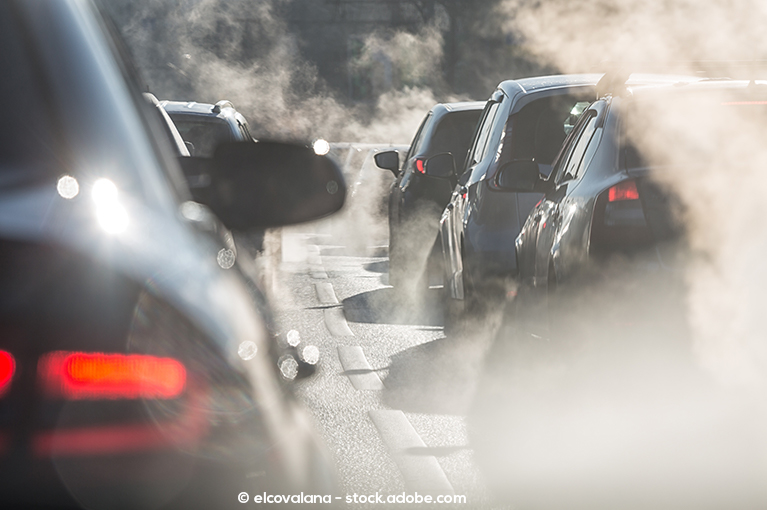 Photo description: Several cars are in traffic, surrounded by the white fumes they created.