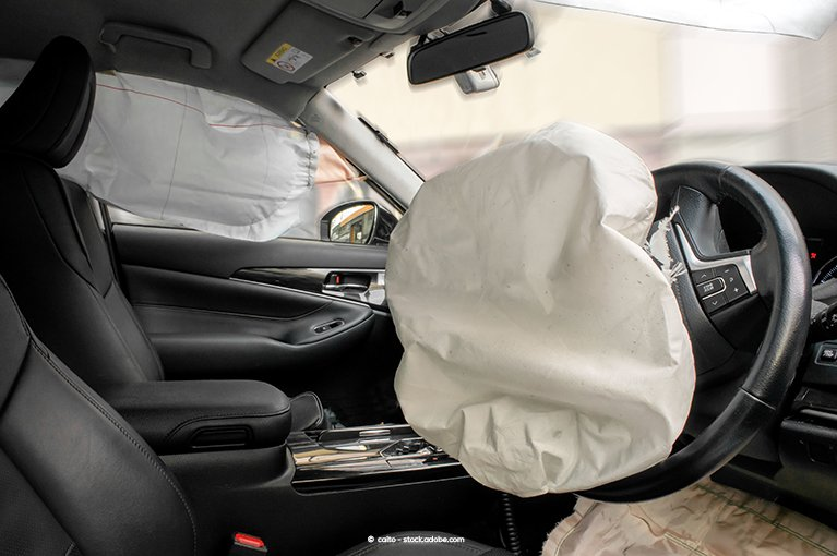 Photo description: An inflated driver side airbag from the view of the front passenger seat.