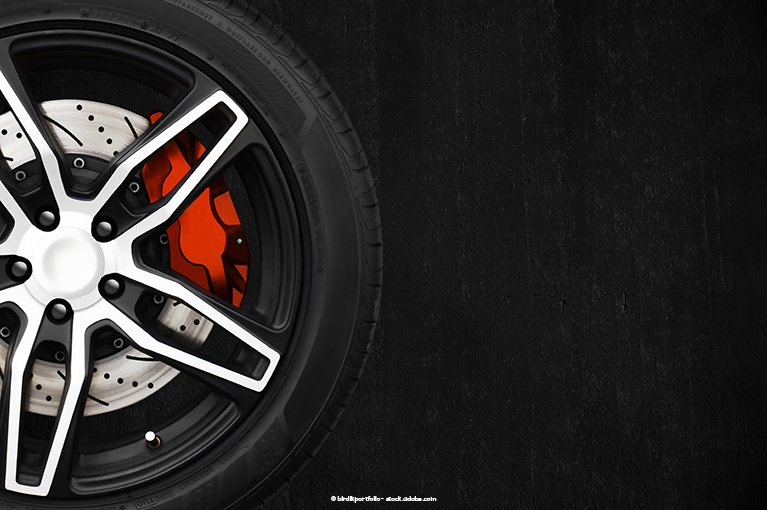 A red brake is attached to a wheel, against a black background.