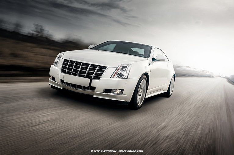 A white car speeds on an empty road.