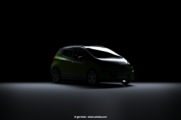 A small car is in an empty space, barely illuminated.