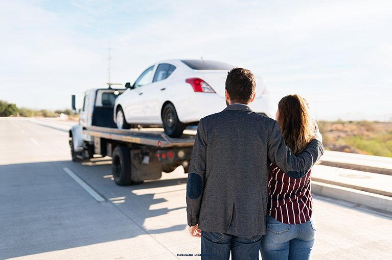 Two people watch as a white car is towed away
