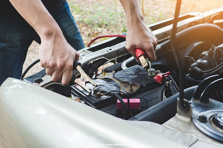 Jumper cables are attached to a car battery.