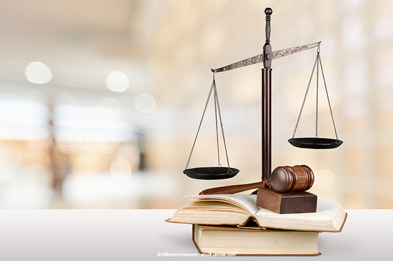 A scale is set atop books, accompanied by a gavel.