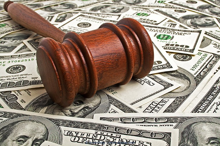 A gavel rests on a pile of money.