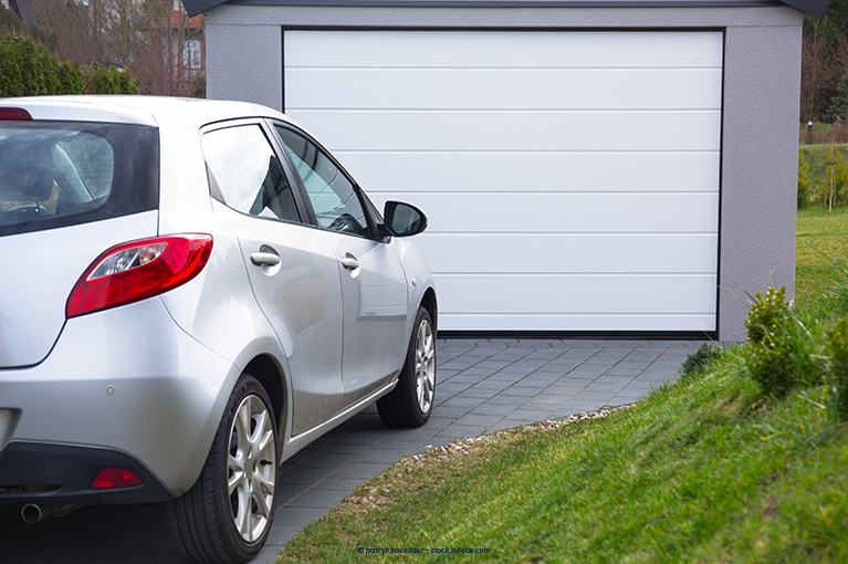 A car is parked outside on a driveway, in front of a garage.