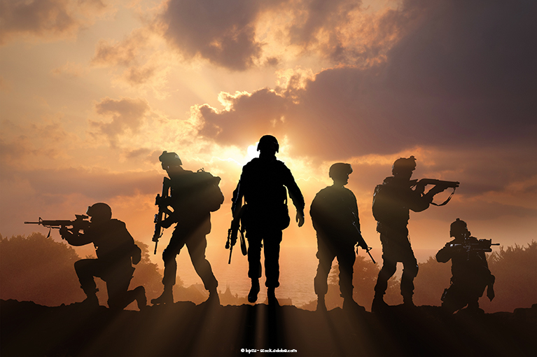 Six armed soldiers stand before the horizon, the sunlight behind them making them appear as shadows.