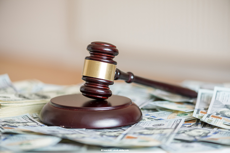 A gavel sits on a pile of cash.