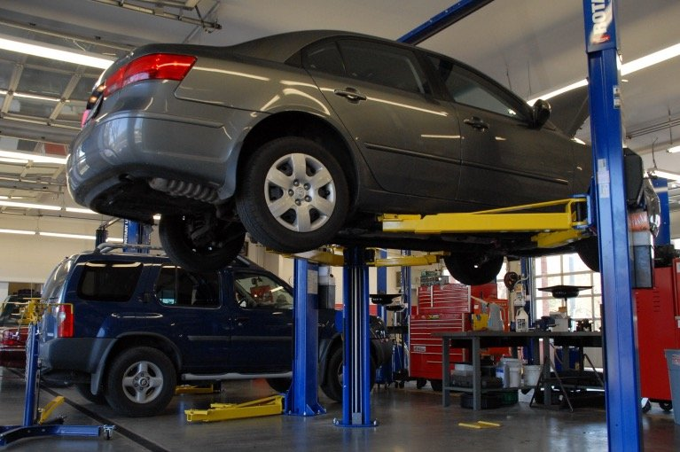 A car is raised up so the underside can be inspected.