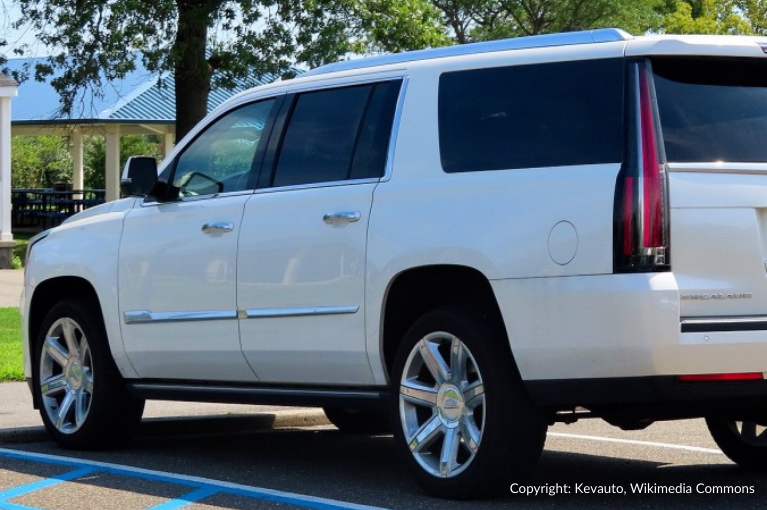 A white Cadillac Escalade is parked outside.