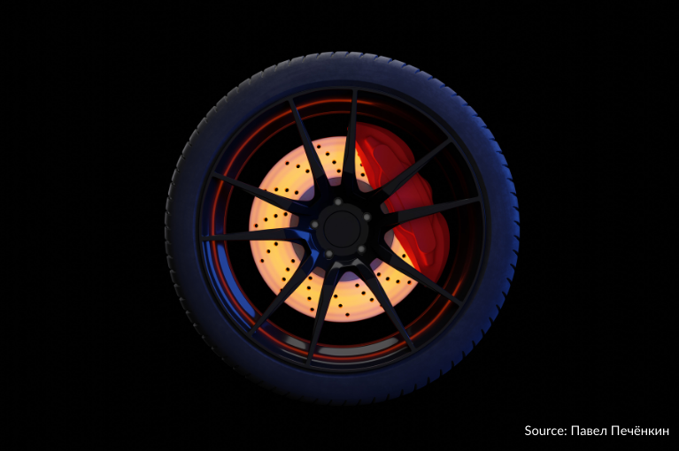 A single wheel is situated against a black background, with a glowing center that illuminates its red brake.