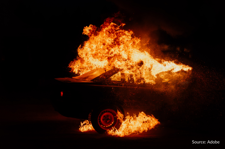 A fire consumes a car in the dark.