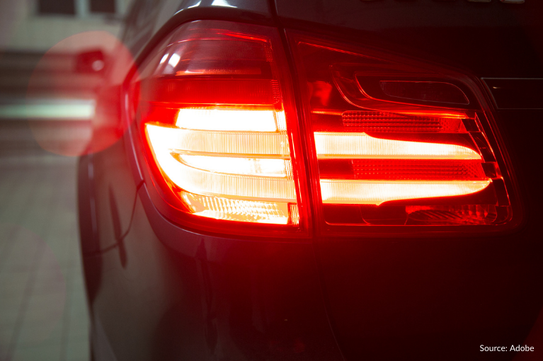 A flashing brake light on the left side of a black car.