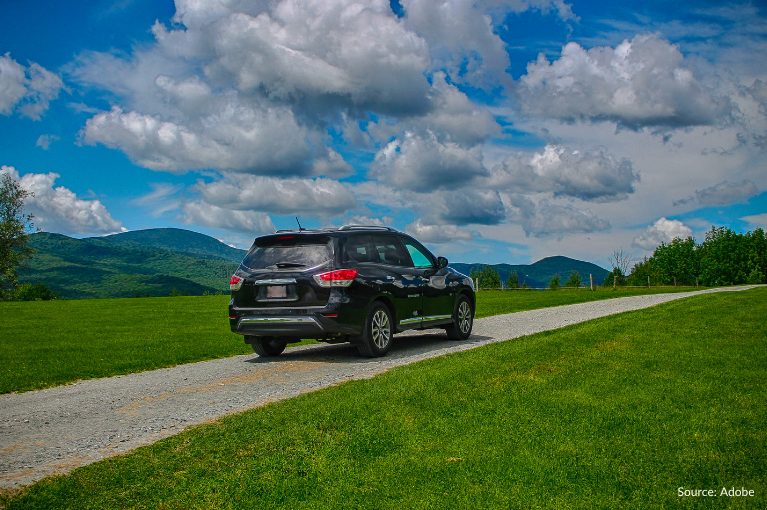 A Nissan Pathfinder is alone on a road, surrounded by grasslands.