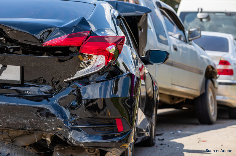 A black car rear-ends a gray car in front, as part of a pile-up on a road.