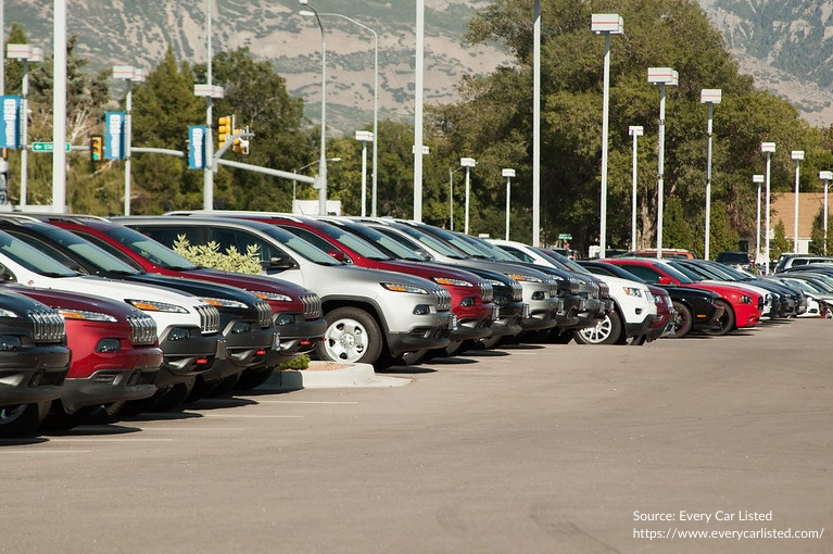 Several cars sit in a row at a dealership