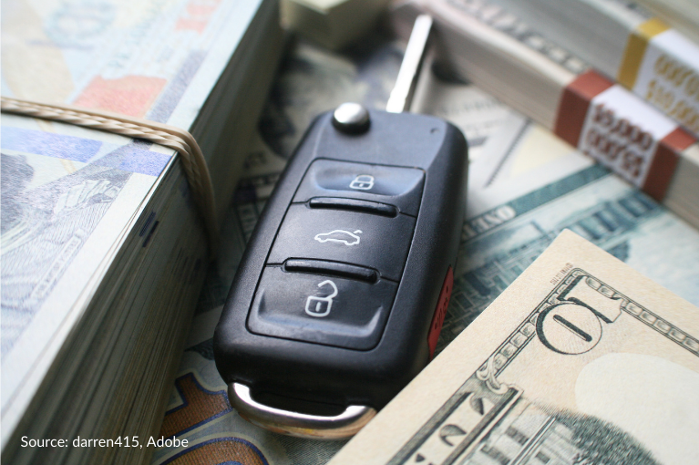 A Volkswagen Jetta key fob sits between two piles of currency.