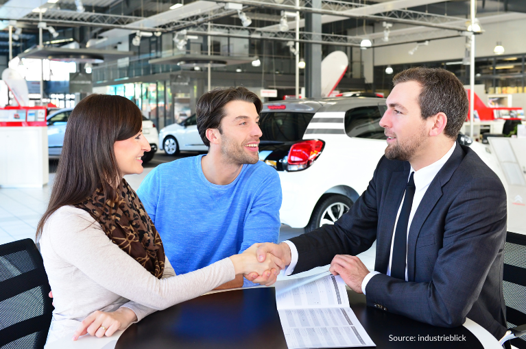 A couple agree to a car sale. A woman shakes hands with a salesperson at the dealership.