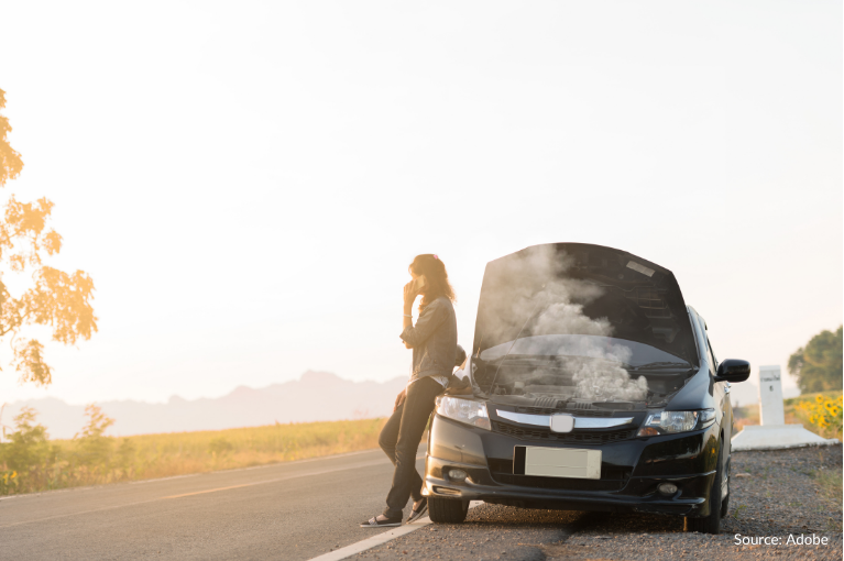 A woman stands beside her car, which has smoke coming out of its engine compartment.