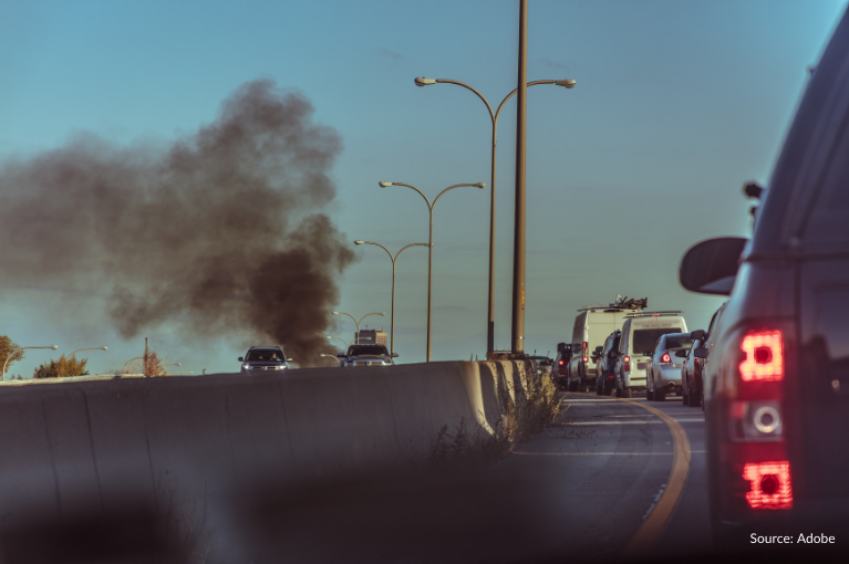A car on the opposite side of the highway emits thick, black smoke.