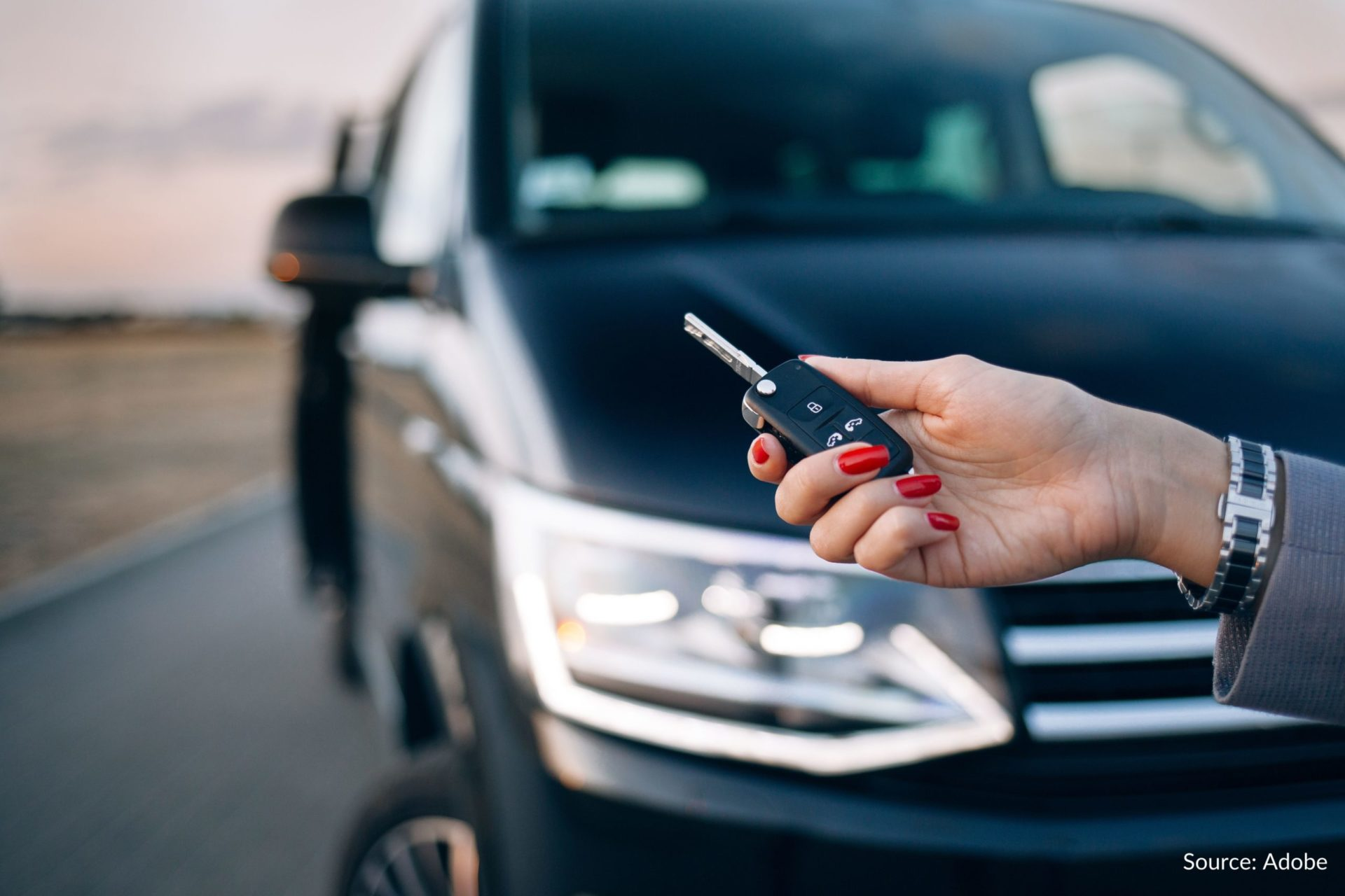 Someone holds a key fob for a black vehicle.