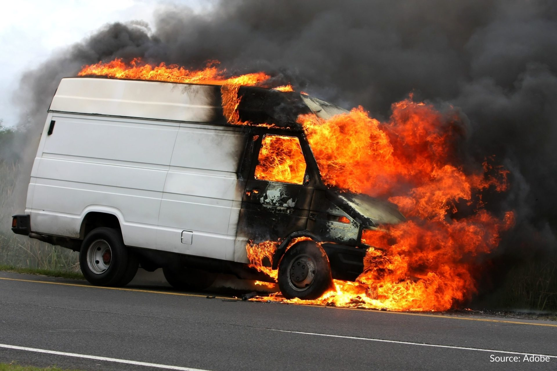 A fire consumes the front portion and roof of a van.