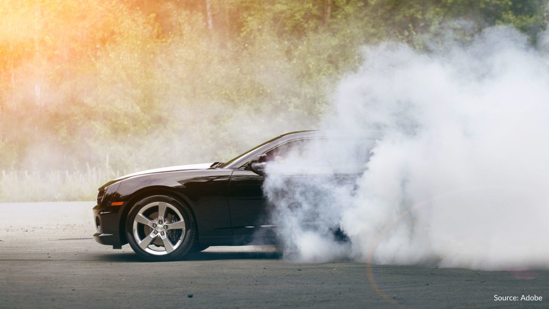 A car speeds, with white smoke clouding the back of the car.